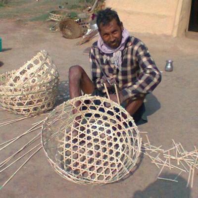 थारु हस्तकलाः गाउँघरमा थारुले घाँस काट्न तथा सरसामान राख्न बाँसको चोयाबाट सामान निर्माण गर्छन् । एक थारु खैंचा बनाउँदै ।